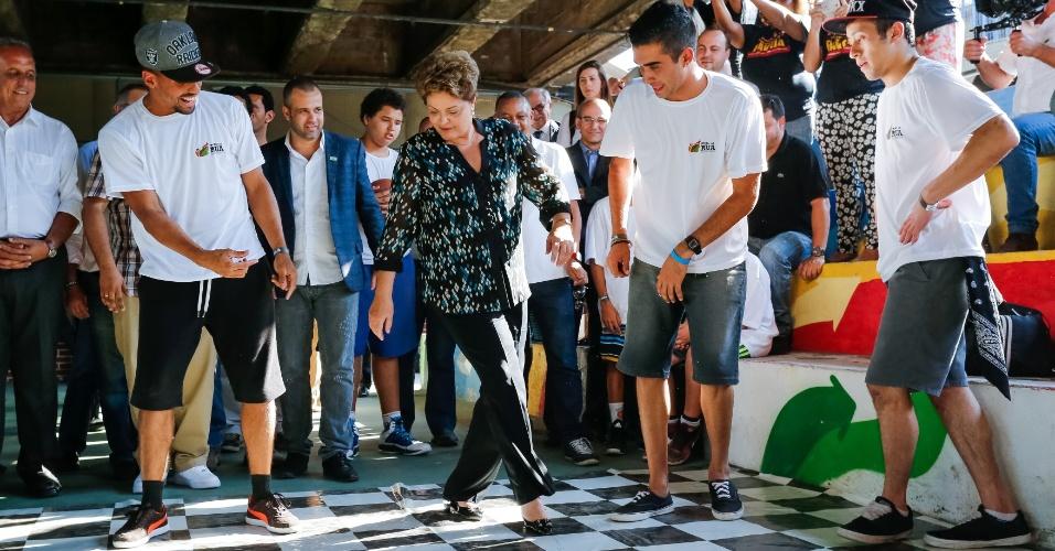 """15.set.2014 - A presidente Dilma Rousseff, candidata à reeleição pelo PT, faz passo de dança de rua no lançamento do livro """"Um País Chamado Favela"""" de Renato Meirelles e Celso Athayde, na Central Única de Favelas (CUFA), em Madureira, no Rio de Janeiro"""