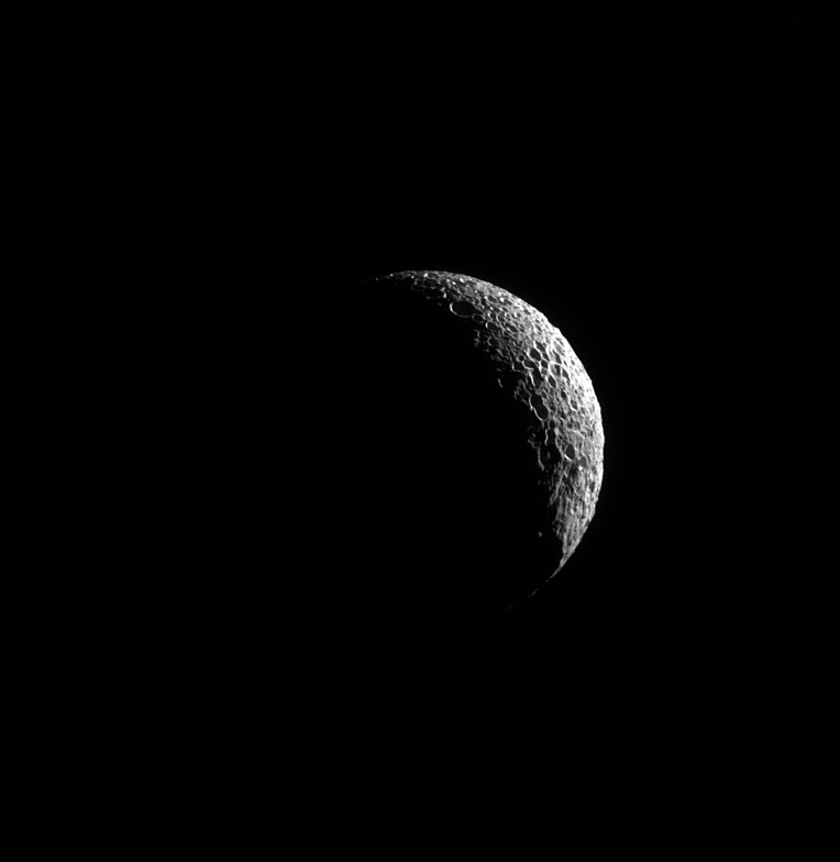 15.set.2014 - Uma lasca fina de Mimas, uma das grandes luas de Saturno, é iluminada, expondo suas muitas crateras e indicando o passado violento da lua. A mais famosa evidência de uma colisão no satélite natural é a cratera Herschel, que da a Mimas a aparência de uma estrela da morte. A imagem foi feita em luz visível com a câmera de ângulo estreito sonda Cassini em 20 de maio de 2013 e divulgada nesta segunda-feira (15) pela Nasa