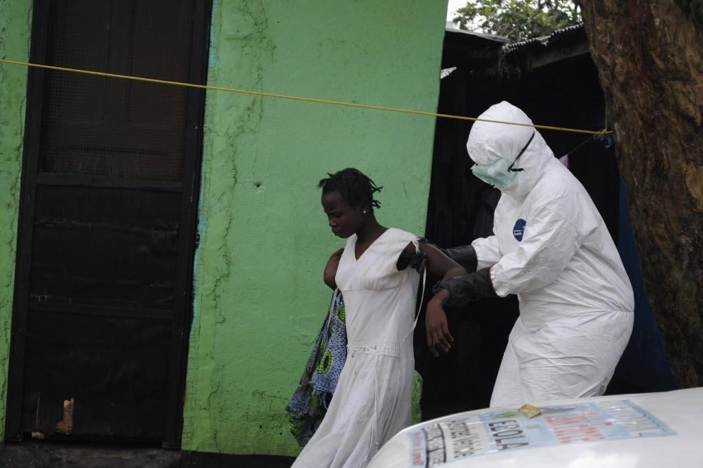 15.set.2015 - Profissional da saúde leva uma mulher com sintomas de contaminação pelo vírus ebola para uma ambulância em Monróvia, Libéria, nesta segunda-feira. A epidemia da febre hemorrágica ebola já matou mais de 2.400 pessoas na África Ocidental, segundo a OMS (Organização Mundial da Saúde)