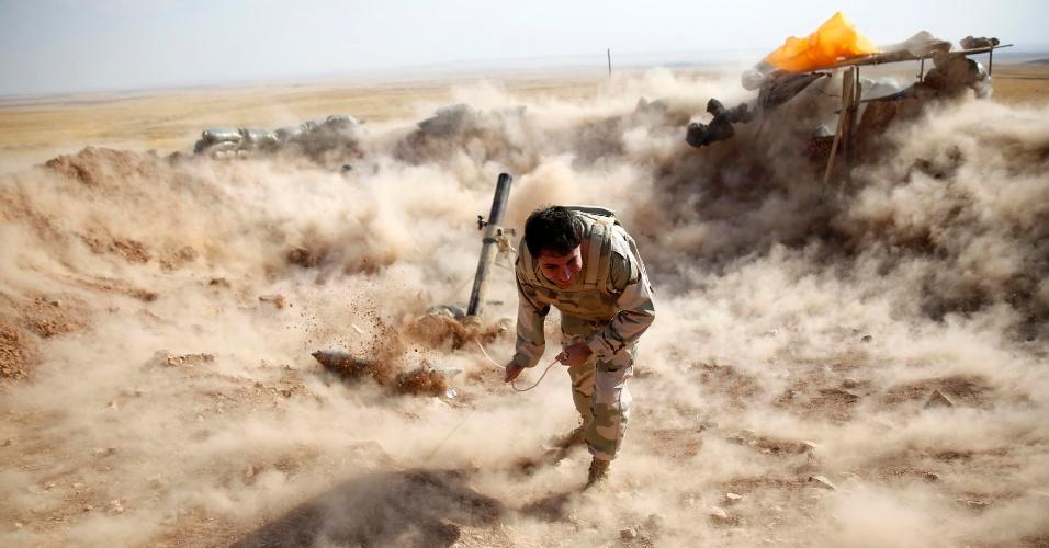 15.set.2014 - Soldado curdo se protege após disparar morteiro em direção a Zummar, região controlada pelo EI (Estado Islâmico) perto de Mosul, no norte do Iraque