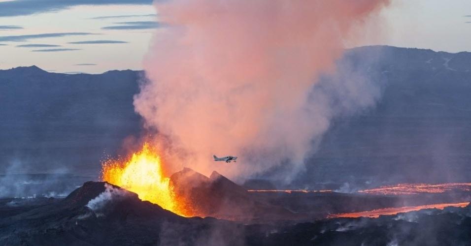 16.set.2014 - A erupção do vulcão Bardarbunga forma um rio de lava no sudeste da Islândia. Em imagem deste domingo (14) divulgada nesta terça-feira (16), mostra avião passando ao lado da lava. O sistema vulcânico do Bardarbunga tem gerado centenas de tremores diários desde meados de agosto, deixando a população em alerta para uma possível explosão. Com 2.000 metros de altitude, o Bardarbunga é o segundo pico mais alto da Islândia