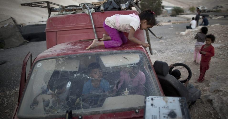 16.set.2014 - Crianças palestinas brincam em veículo abandonado em acampamento da tribo beduína Jahalin, no deserto da Judeia, na Cisjordânia. Segundo relatos da imprensa local, o governo de Israel planeja retirar os palestinos desta região e transferí-los para uma área no Vale do Jordão