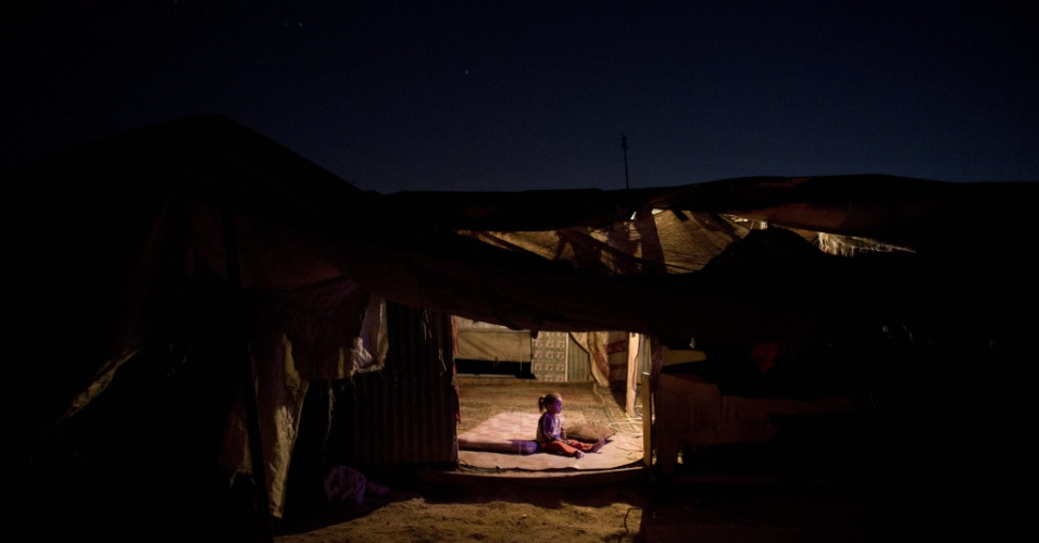 16.set.2014 - Menina palestina da tribo beduína Jahalin assiste televisão durante o anoitecer no deserto da Judeia, na Cisjordânia. Segundo relatos da imprensa local, o governo de Israel planeja retirar os palestinos desta região e transferí-los para uma área no Vale do Jordão