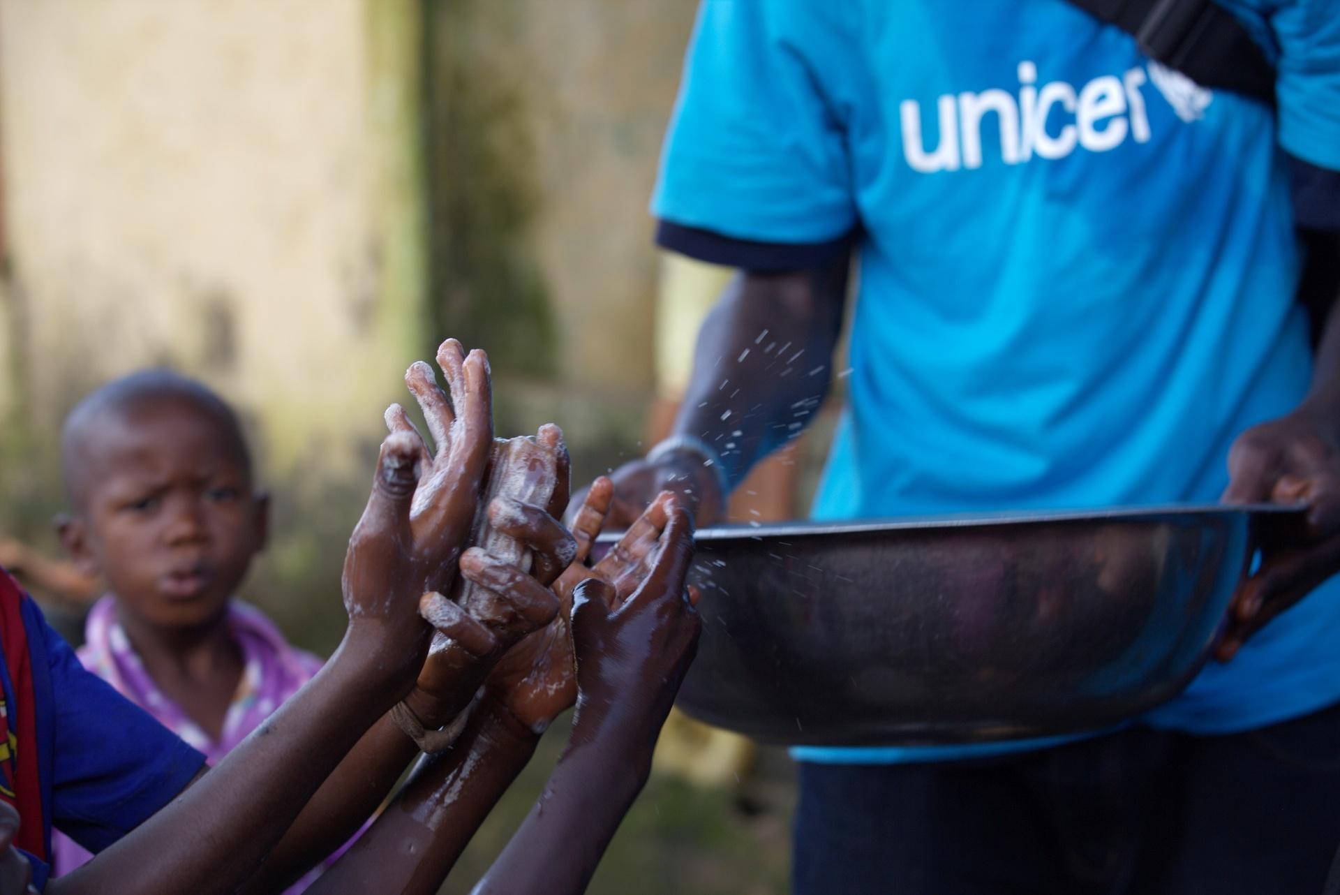 17.set.2014 - Agente de saúde carrega bacia de água para conscientizar as crianças de que é preciso lavar as mãos para prevenir a propagação do ebola, nesta quarta-feira (17), em Conacri, na Guiné. Segundo a OMS (Organização Mundial de Saúde), o número de casos da doença na África Ocidental pode dobrar a cada três semanas e acabar custando quase US$ 1 bilhão para conter a crise
