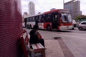 Mulher aguarda ônibus em banco de ponto na estação Faria Lima