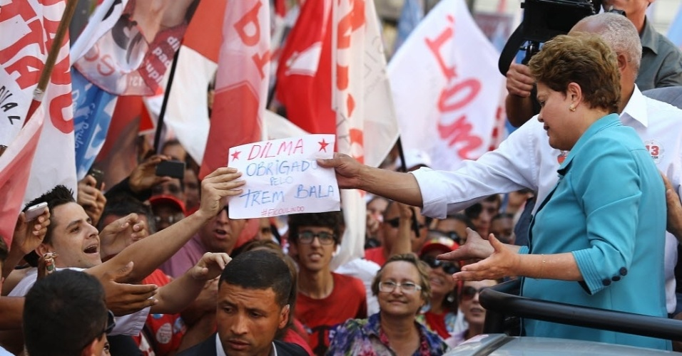 """17.set.2014 - Eleitor de Dilma Rousseff em 2010, estudante Benedito Pereira Lima entrega cartaz de protesto durante visita da candidata do PT a Campinas. """"Dilma, obrigado pelo trem-bala. #FicouLindo"""", ironizou o estudante, que disse que Dilma ficou surpresa e """"virou a cara"""" para seu protesto"""