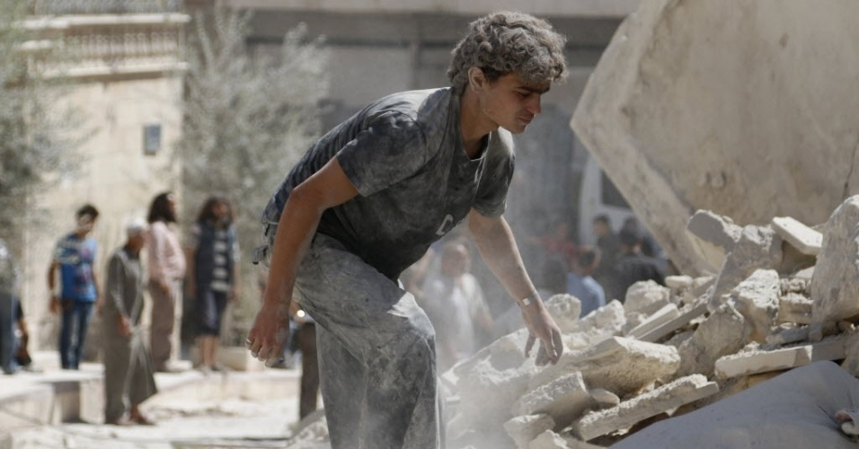 18.set.2014 - Homem busca sobreviventes sob os escombros de edifícios destruídos pela explosão de uma bomba, lançada pelas forças do ditador sírio Bashar Assad em Maarat Al-Nouman, sul de Idlib