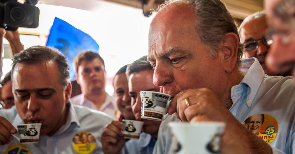 18.set.2014 - O candidato ao governo de Minas Gerais pelo PSDB, Pimenta da Veiga, toma café ao lado de comerciantes e políticos durante campanha em Caratinga, no Vale do Rio Doce, nesta quinta-feira (18)