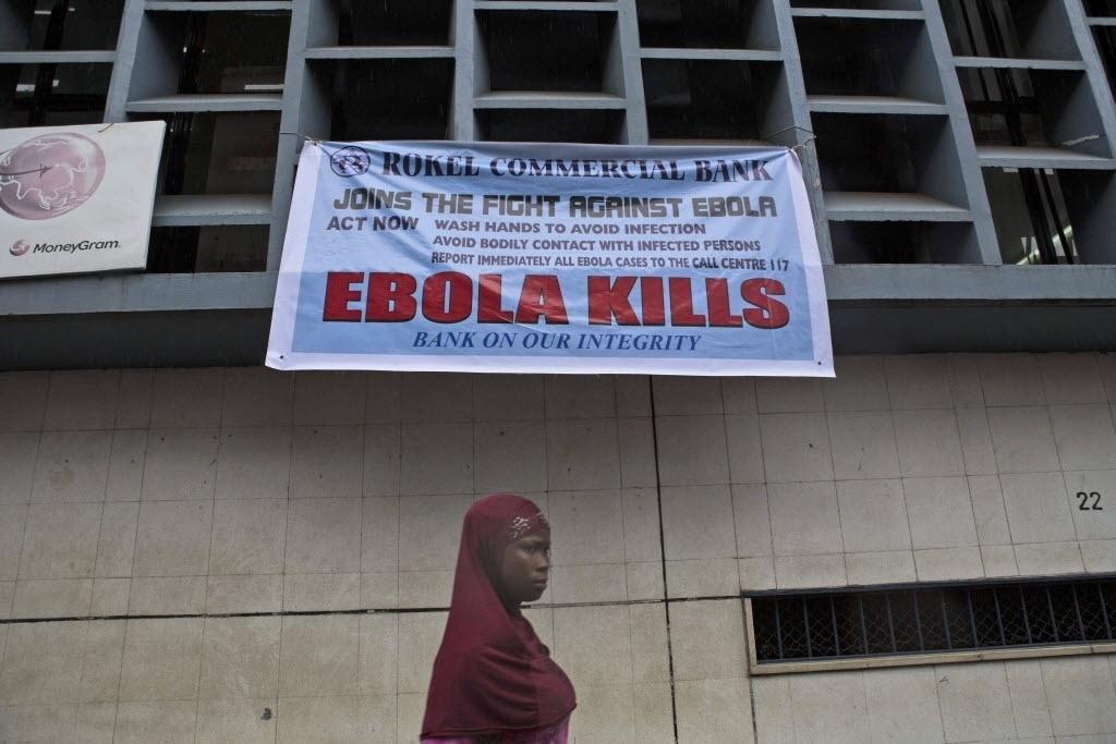18.set.2014 - Uma mulher passa sob uma placa de alerta sobre o vírus ebola em Freetown, em Serra Leoa, nesta quinta-feira. Casos de Ebola na Libéria, Serra Leoa e Guiné continuam aumentando, conforme  divulgado hoje pela OMS (Organização Mundial da Saúde), que atualizou para 2.622 o novo número de mortos