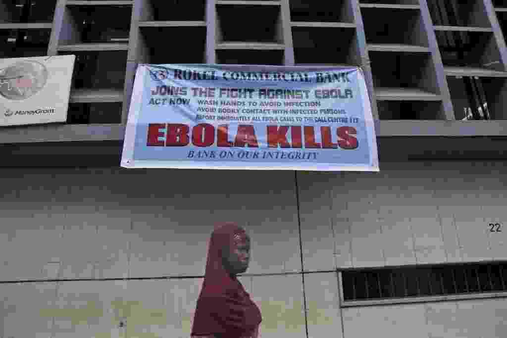 18.set.2014 - Uma mulher passa sob uma placa de alerta sobre o vírus ebola em Freetown, em Serra Leoa, nesta quinta-feira. Casos de Ebola na Libéria, Serra Leoa e Guiné continuam aumentando, conforme  divulgado hoje pela OMS (Organização Mundial da Saúde), que atualizou para 2.622 o novo número de mortos - Tanya Brinda/ Efe