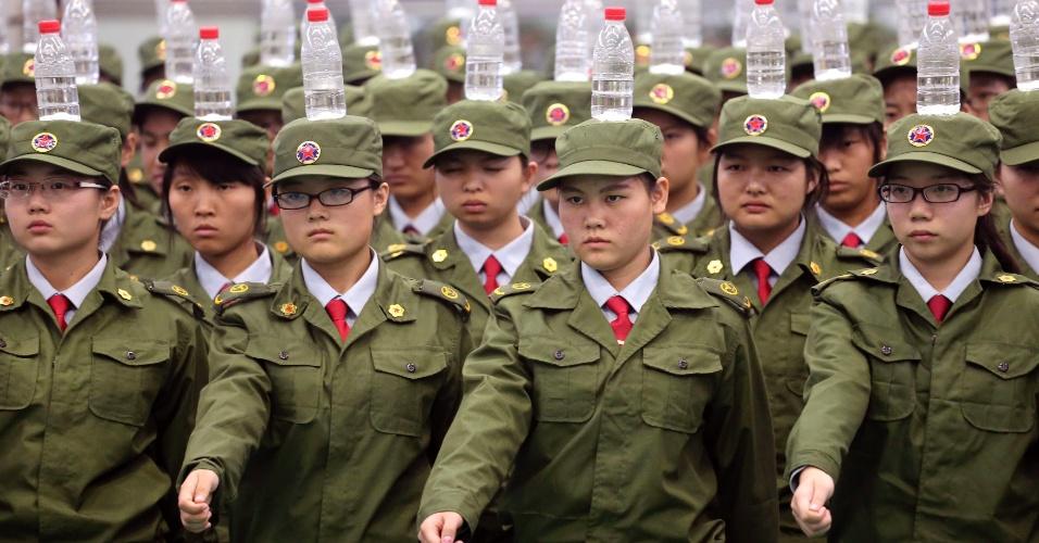 19.set.2014 - Estudantes marcham equilibrando garrafas de água na cabeça durante treinamento militar em uma escola de Zhengzhou, na província chinesa de Henan