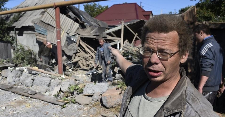 19.set.2014 - Homem aponta para casa destruída no distrito Oktiabrskiy, leste de Donetsk, na Ucrânia. Pelo menos quatro foguetes atingiram três casas durante a noite. A região ainda é controlada por militantes pró-Rússia