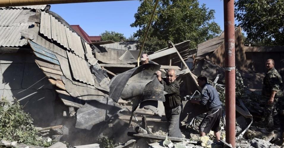 19.set.2014 - Homens retiram escombros de casa que foi atingida por um foguete no distrito Oktiabrskiy, no leste da cidade ucraniana de Donetsk. Pelo menos quatro foguetes atingiram três casas durante a noite. Um homem morreu. A região ainda é controlada por militantes pró-Rússia