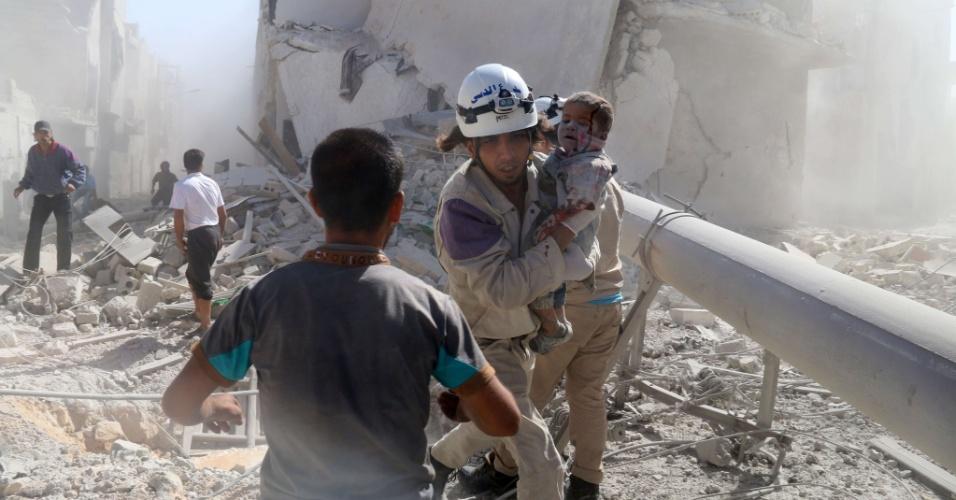 20.set.2014 - Homem resgata criança que ficou ferida após ataque de forças do governo com uma bomba barril em um bairro controlado por rebeldes na cidade de Aleppo, na Síria, neste sábado (20)