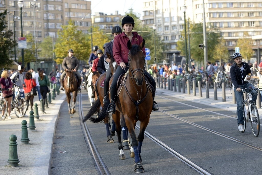 21.set.2014 - Cavalos e bicicletas tomam as ruas do centro de Bruxelas, na Bélgica, na Semana da Mobilidade. O centro da capital belga foi transformado em uma zona livre de carros, na qual apenas moradores podem trafegar com veículos. Mesmo assim, a velocidade na área foi limitada a 30 km/h