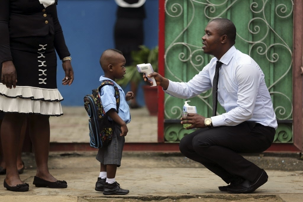 22.set.2014 - Funcionário de uma escola mede a temperatura de um aluno com um termômetro infravermelho digital na retomada das aulas nas escolas privadas em Lagos, no sudoeste da Nigéria, nesta segunda-feira