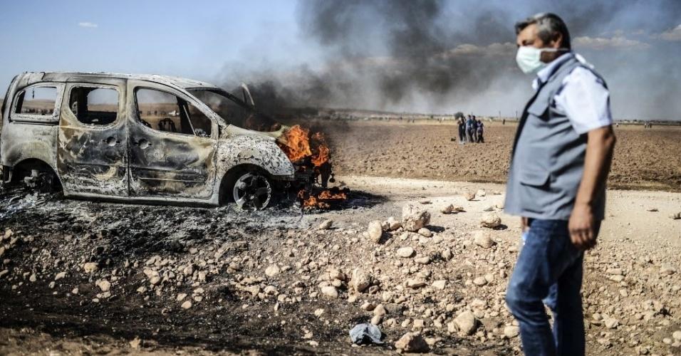 22.set.2014 - Homem caminha ao lado de carro em chamas após confrontos na cidade turca de Suruc entre manifestantes e a polícia. A Turquia decidiu bloquear trechos de sua fronteira com a Síria após receber uma onda de mais de 130 mil sírios, nos últimos dias, fugindo das perseguições do grupo radical Estado Islâmico