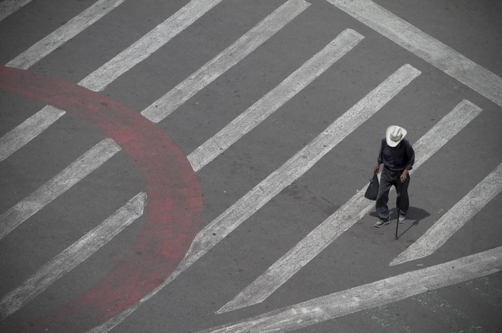 22.set.2014 - Homem caminha por rua vazia em frente à praça da Constituição, no centro da Cidade do México. Por conta do Dia Mundial sem Carro, as autoridades locais proibiram a circulação de automóveis pela área, sendo permitida apenas a passagem de pedestres e ciclistas