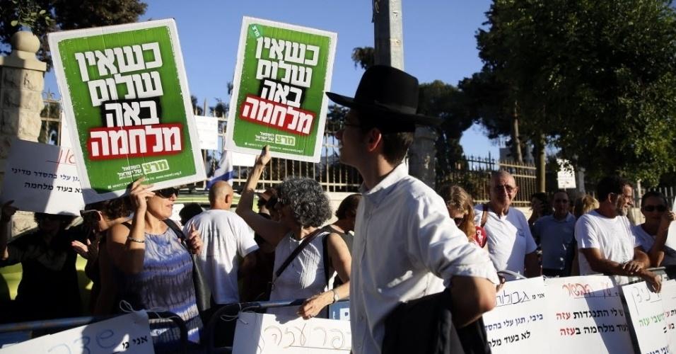 22.set.2014 - Israelenses que vivem perto da faixa de Gaza e ativistas carregam cartazes com a frase
