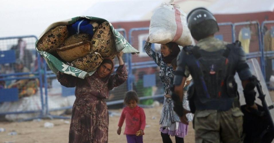 22.set.2014 - Mulheres curdas carregam pertences após cruzarem a fronteira entre a Síria e a Turquia em Suruc. A Turquia decidiu bloquear trechos de sua fronteira com a Síria após receber uma onda de mais de 130 mil sírios, nos últimos dias, fugindo das perseguições do grupo radical Estado Islâmico