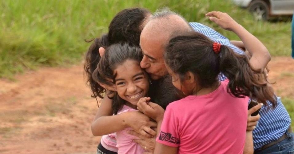 22.set.2014 - O candidato do DEM ao governo do Acre, Tião Bocalom, abraça e beija crianças durante caravana para visitar moradores e comerciantes da estrada Transacreana