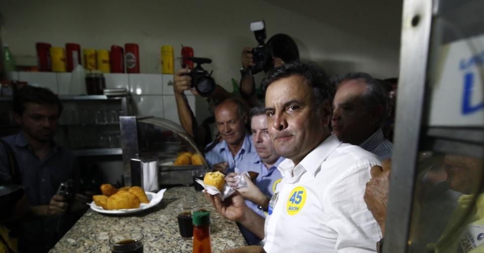 """22.set.2014 - O candidato do PSDB à Presidência, Aécio Neves, come uma coxinha em uma lanchonete no bairro Eldorado, em Contagem, na região metropolitana de Belo Horizonte, onde faz campanha nesta segunda-feira. Seguindo a estratégia de priorizar seu Estado natal para estancar a perda de votos, Aécio fez um apelo para que """"mineiros de todos os cantos do Estado redobrem os esforços"""" na reta fina de campanha"""