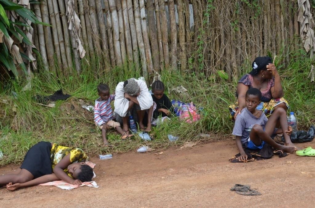 23.set.2014 - Liberiana infectada pelo vírus ebola deita em uma estrada em frente ao