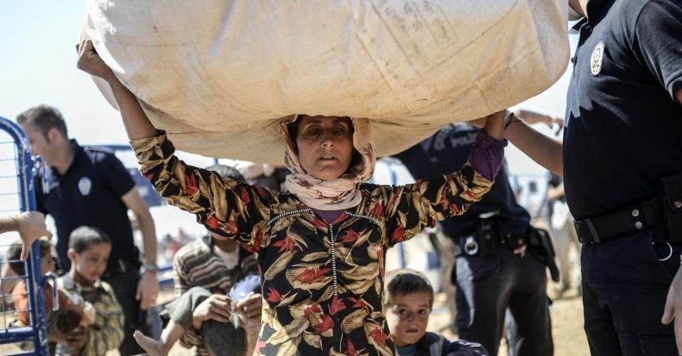 23.set.2014 - Mulher carrega seus pertences na fronteira entre a Síria e a Turquia na cidade de Suruc, na província de Sanliurfa. A ONU alertou que 400 mil pessoas devem tentar entrar na Turquia fugindo da violência do Estado Islâmico