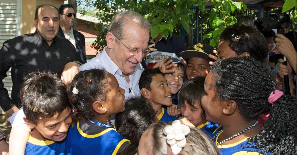 O governador e candidato à reeleição, Tarso Genro (PT), recebe o carinho de crianças durante caminhada em Porto Alegre, no bairro do Rubem Berta, nesta terça-feira