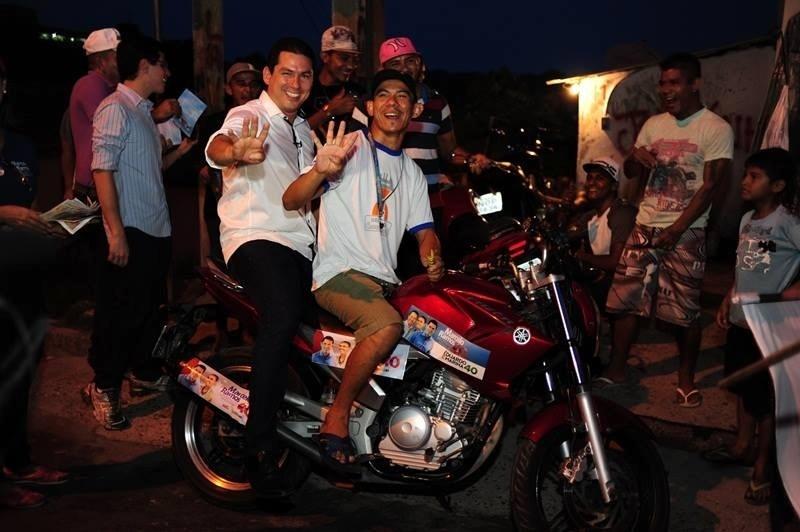 17.set.2014 - Marcelo Ramos (esq.), candidato ao governo do Amazonas pelo PSB, posa para foto com apoiador em cima de uma moto