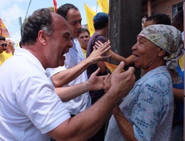21.set.2014 - Neste domingo, o candidato do PSB ao Senado em Pernambuco, Fernando Bezerra Coelho, caminhou pelas ruas de Brasília Teimosa, ao lado de Paulo Câmara (ao fundo), candidato ao governo do Estado pelo mesmo partido