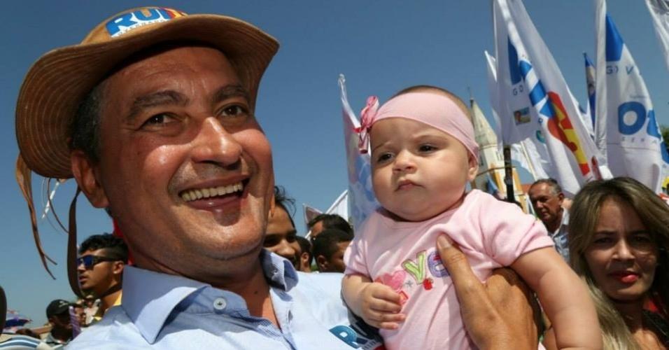 22.set.2014 - O candidato ao governo da Bahia pelo PT, Rui Costa, segura criança durante caminhada em Uauá, no interior do Estado