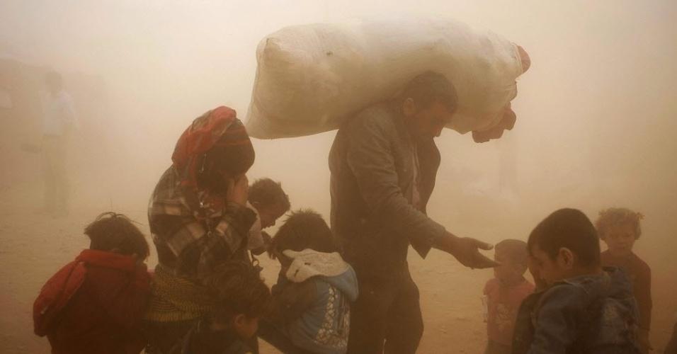24.fev.2014 - Refugiados sírios passam por tempestade de areia na fronteira com Turquia.  Os Estados Unidos e aliados árabes bombardearam a Síria pela primeira vez na terça-feira (23), abrindo uma nova frente contra os militantes entrando na guerra civil que já dura três anos na Síria