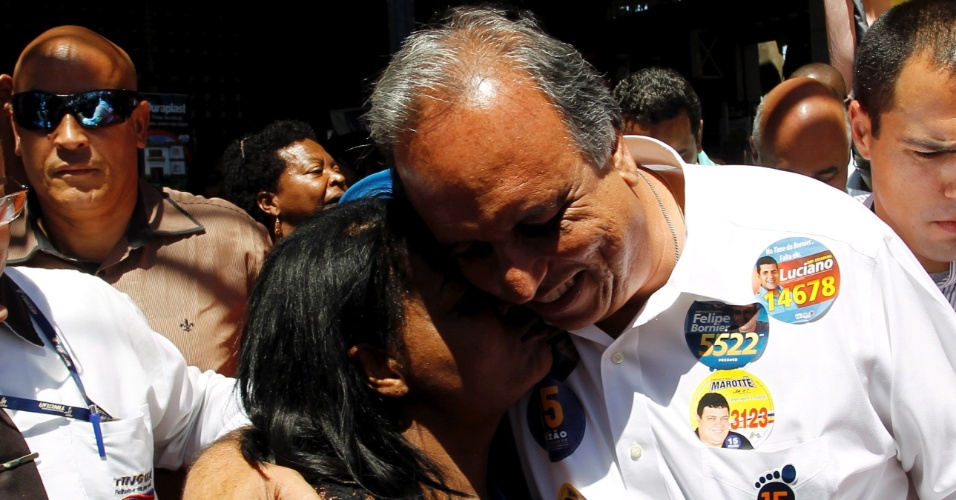24.set.2014 - O governador do Rio de Janeiro e candidato a reeleição pelo PMDB, Luiz Fernando Pezão, recebe o carinho de uma eleitora durante caminhada em Nova Iguaçu, na Baixada Fluminense