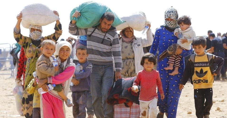 24.set.2014 - Refugiados curdos caminham para cruzar a fronteira entre a Síria e a Turquia na cidade de Suruc, na província de Sanliurfa. A ONU alertou que 400 mil pessoas devem tentar entrar na Turquia fugindo da violência do Estado Islâmico