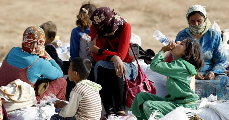 24.set.2014 - Refugiados sírios esperam para cruzar a fronteira entra a Síria e Turquia na cidade de Suruc, na província de Sanliurfa. Na noite da última terça-feira (23), a coalizão dirigida pelos Estados Unidos bombardeou posições jihadistas nos arredores da cidade curda de Ain al-Arab, completamente cercada pelo grupo Estado Islâmico (EI), influenciando no número de pessoas que tenta deixar a região.