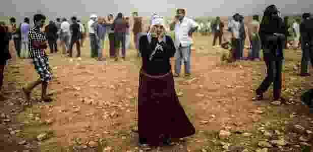 24.set.2014 - Uma mulher síria curda em tempestade de areia em uma colina onde e ela e outras pessoas observavam confrontos entre jihadistas do Estado Islâmico e combatentes curdos, no vilarejo de Swedi, a 10 km a oeste de Suruc, na província de Sanliurfa, na Síria - Bulent Kilic/AFP