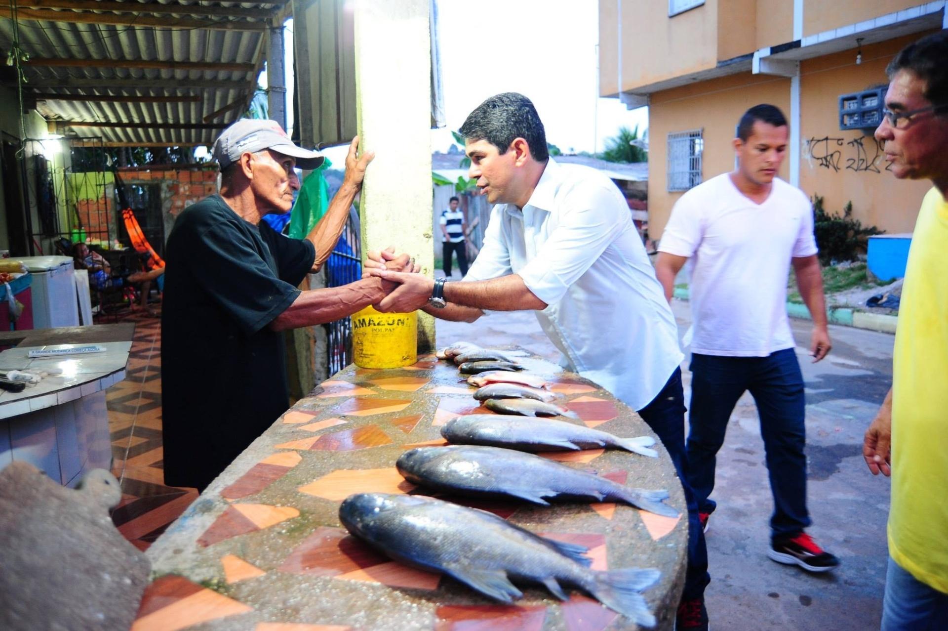26.ago.2014 - Marcelo Ramos (esq.), candidato ao governo do Amazonas pelo PSB, visita mercado e cumprimenta comerciante durante campanha eleitoral
