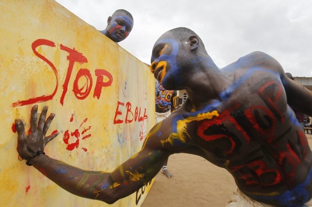 25.set.2014 - Ator que interpreta papel de uma vacina contra o vírus ebola marca uma lona com as mãos sujas de tinta durante uma performance em uma escola em Abidjan, capital da Costa do Marfim, que faz parte de uma campanha contra a epidemia