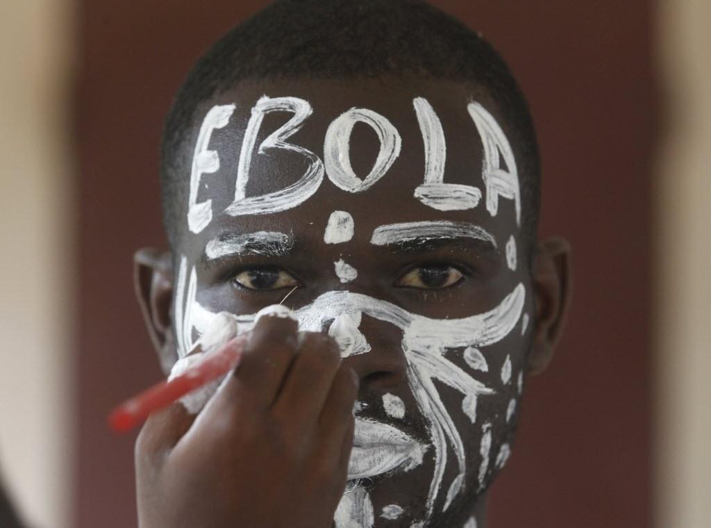 25.set.2014 - Ator que representa o papel do vírus ebola pinta o rosto para uma performance em uma escola em Abidjan, capital da Costa do Marfim, durante uma campanha contra a epidemia
