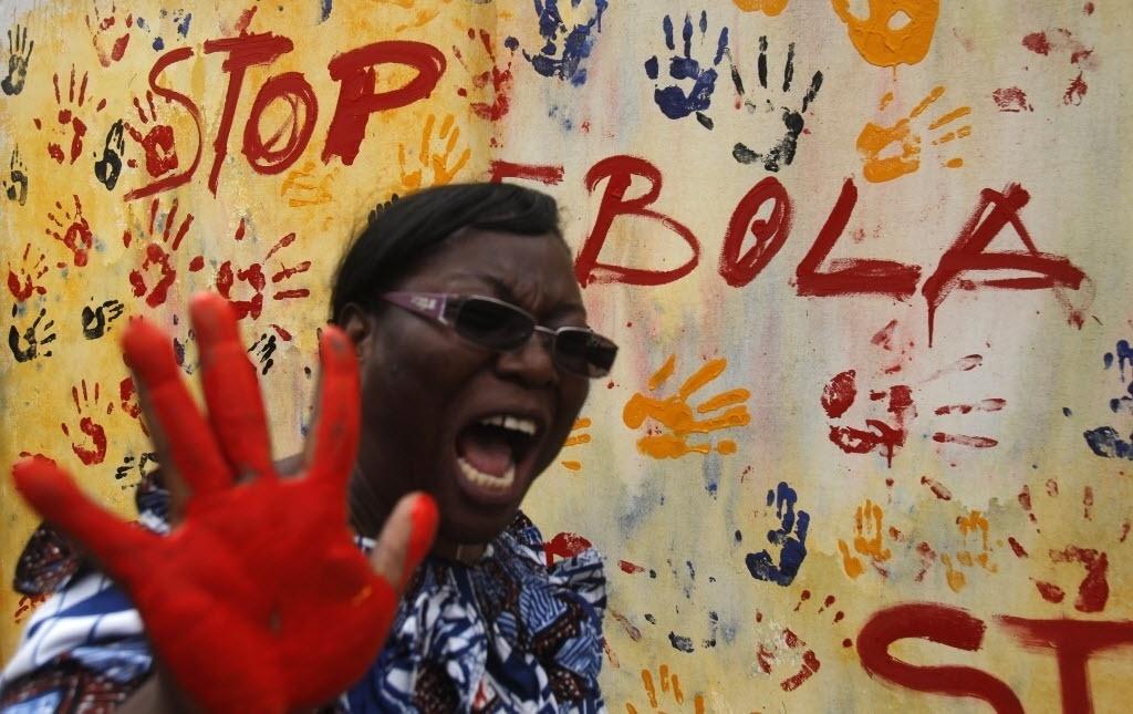 25.set.2014 - Professora de uma escola em Abidjan, capital da Costa do Marfim, exibe as mãos sujas de tinta antes de marcar uma lona em uma campanha contra a epidemia
