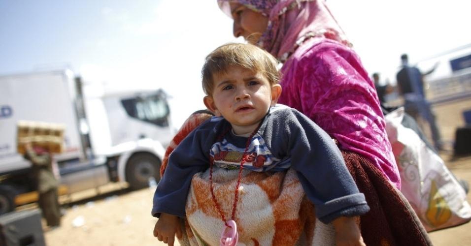25.set.2014 - Refugiada curda carrega seu filho pela fronteira entre a Síria e a Turquia na cidade de Suruc, na província de Sanliurfa. A ONU alertou que 400 mil pessoas devem tentar entrar na Turquia fugindo da violência do Estado Islâmico. Desde o último fim de semana, 138 mil sírios atravessaram a fronteira em direção à Turquia, de acordo com o Alto Comissariado da ONU para Refugiados. A preocupação da agência é com centenas de milhares de pessoas que continuam a viver com medo da perseguição perpetrada pelo grupo contra religiosos e minorias étnicas em outros locais