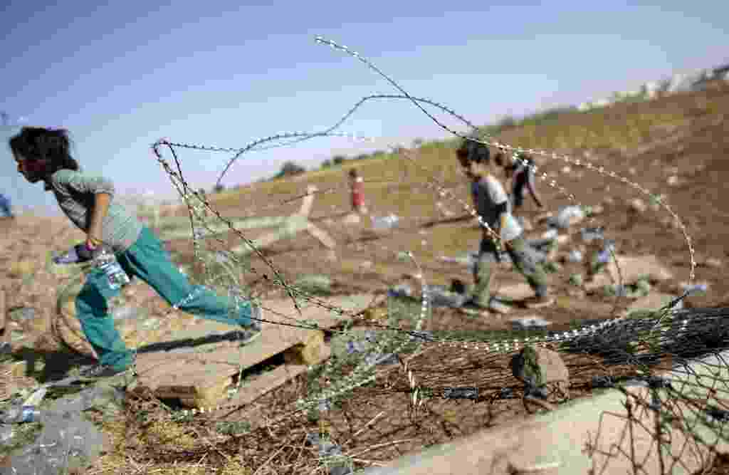 """26.set.2014 - Crianças curdas atravessam a fronteira entre Síria e Turqia, para o lado turco, perto de Sanliurfa. Militantes do grupo que se autodenomina """"Estado Islâmico"""" ampliaram o cerco nesta sexta-feira à cidade síria de Kobani, perto da fronteira com a Turquia, onde entraram em confronto com forças curdas. Os confrontos eram visíveis do território turco, onde alguns manifestantes chegaram a cruzar uma cerca na fronteira para defender a cidade - Murad Sezer / Reuters"""