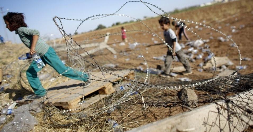 26.set.2014 - Crianças curdas atravessam a fronteira entre Síria e Turqia, para o lado turco, perto de Sanliurfa. Militantes do grupo que se autodenomina