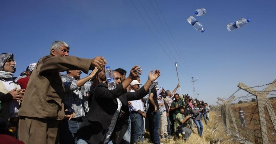 26.set.2014 - Curdos lançam garrafas de água da Turquia para a Síria, na cerca que delimita a fronteira entre os dois países. Militantes do grupo que se autodenomina