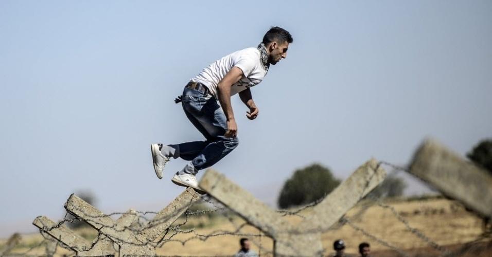26.set.2014 - Homem curdo salta sobre cerca na fronteira entre Turquia e Síria, perto de Sanliurfa. Militantes do grupo que se autodenomina