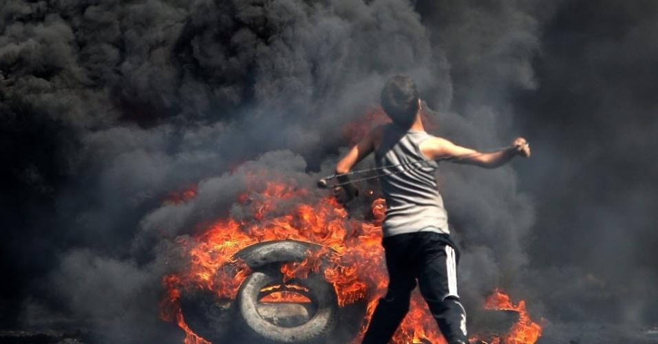 26.set.2014 - Manifestante palestino atira pedras em direção aos soldados israelenses durante uma manifestação contra a desapropriação de terras palestinas por Israel, na aldeia de Kafr Qaddum, perto de Nablus, na Cisjordânia ocupada