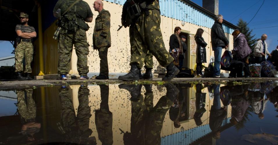 26.set.2014 - Passageiros que saíram de ônibus de Donetsk, na Ucrânia, rumo a Rostov, na Rússia, aguardam enquanto suas bagagens são inspecionadas por rebeldes em posto de checagem na fronteira entre os dois países. O presidente ucraniano Petro Poroshenko ordenou o fechamento temporário da fronteira porosa do país com a Rússia. Cerca de 260 km da divisa são controlados por forças separatistas em Donetsk e Luhansk