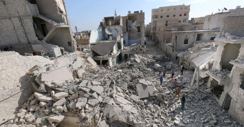 26.set.2014 - Sírios andam por edifícios destruídos após ataques com bombas de tambor atribuídos a forças do governo, no norte da cidade de Aleppo. De acordo com o Observatório Sírio para os Direitos Humanos, ao menos 180 mil pessoas foram mortas desde o início do conflito, em março de 2011. Bombas de tambor são normalmente montadas a partir de grandes tambores de óleo, cilindros de gás e caixas d'água. Eles são preenchidos com explosivos e sucata de metal, para aumentar a fragmentação