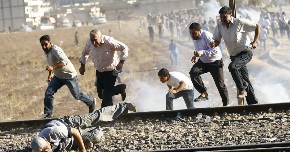 26.set.2014 - Turcos e sírios curdos fogem de gás lacrimogêneo lançado por homens da força de segurança turca na fronteira com a Síria. Militantes do grupo que se autodenomina